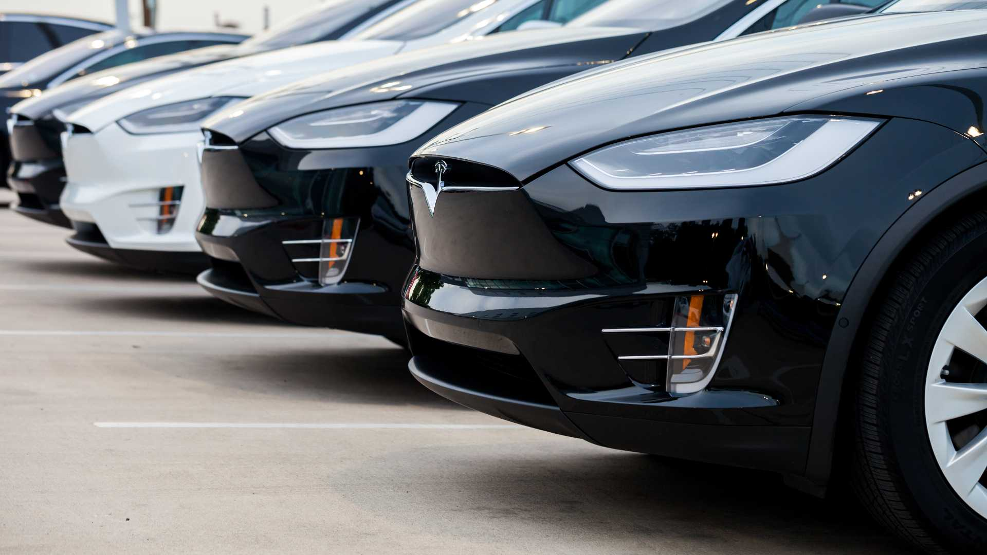 Row of new Tesla Model X electric cars in front of dealership