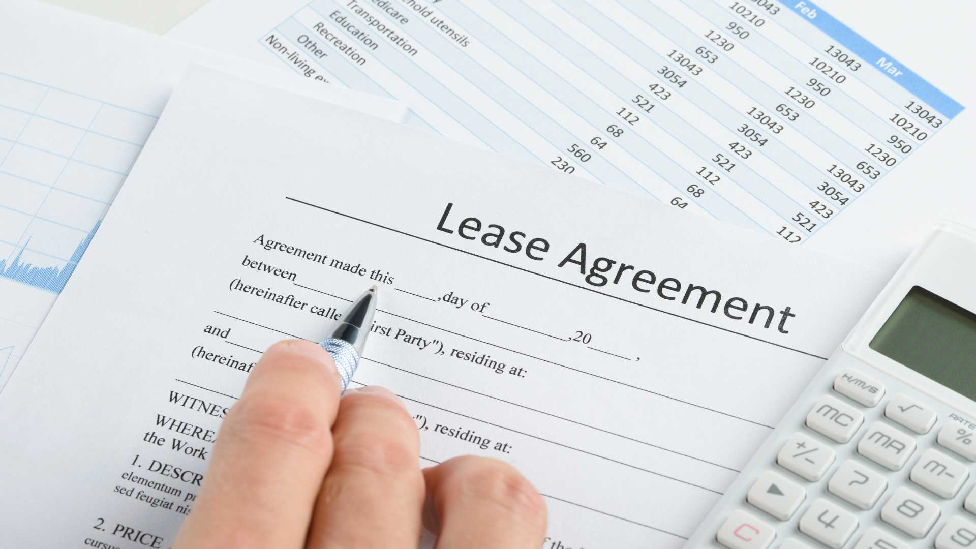 Filling out lease agreement with calculator and expenses